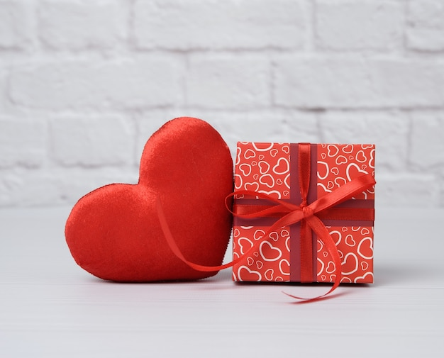 Red cardboard box with gift and plush heart, white background, close up