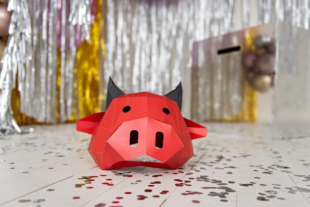 Красная картонная маска быка лежит на серебряном полу
