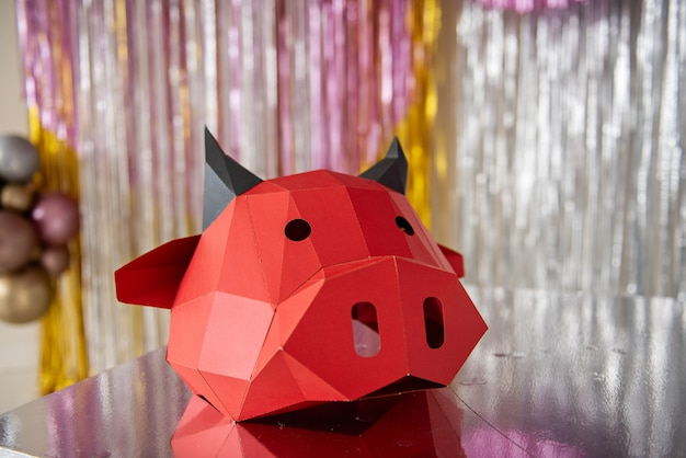 Red cardboard bull mask lies on a silver floor