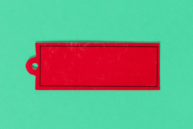 Red cardboard label tag on colored background