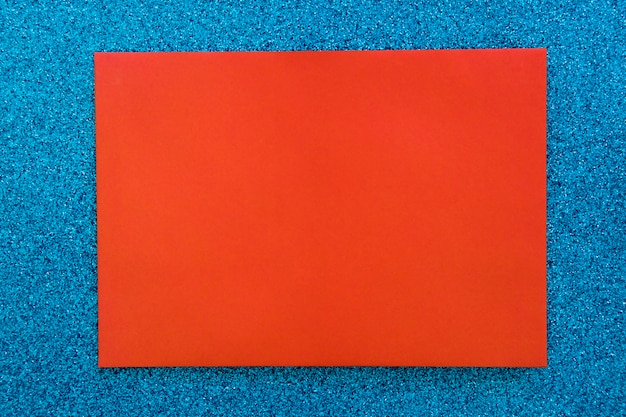 Red cardboard paper on blue glitter background
