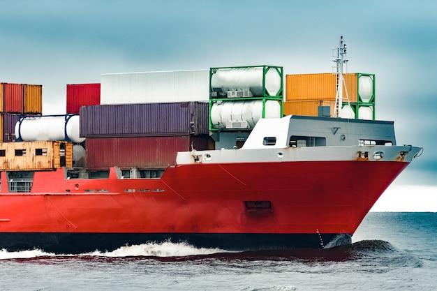 曇りの日の赤い貨物コンテナ船の船首