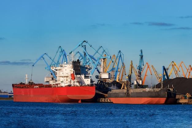 ヨーロッパのリガ港に積み込まれる赤い貨物船