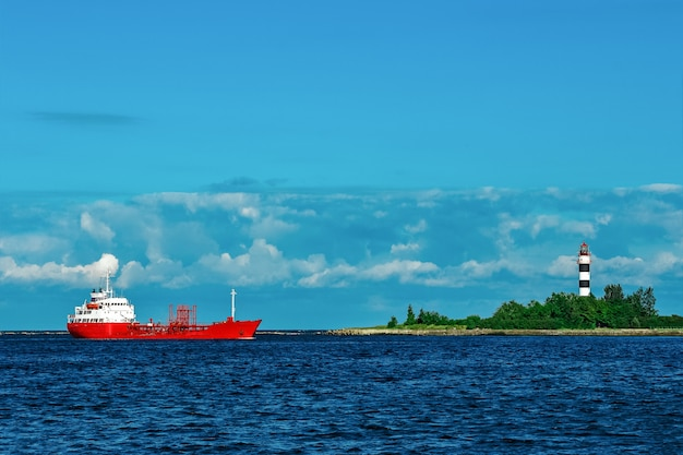 Red cargo tanker ship moving by the river