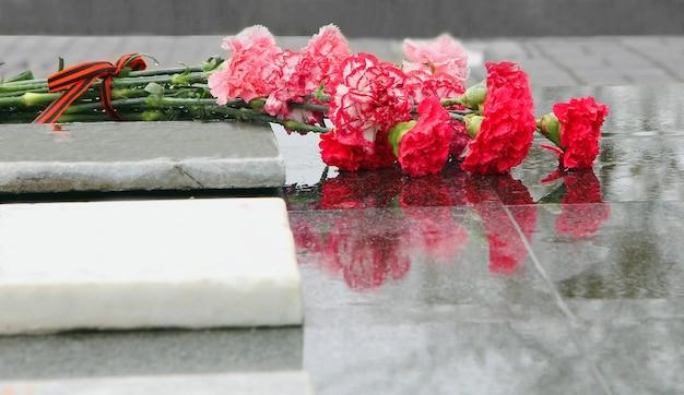 Красные цветы гвоздики лежат на сером мраморе памятника в дождливый день