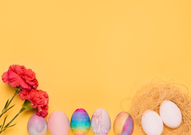 Red carnation flowers with colorful easter eggs on yellow background