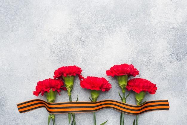 Красные гвоздики и георгиевская ленточка на бетонном фоне.
