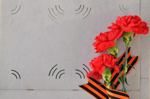 Красные гвоздики и георгиевская лента на фоне старого фотоальбома. день памяти и воинской славы.