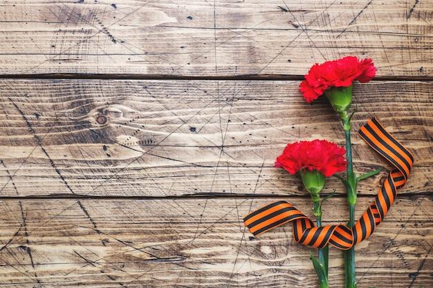 Красные гвоздики и георгиевская ленточка на деревянных фоне.