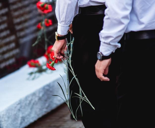 Красные гвоздики в руках мужчин в черных брюках и белых рубашках, идущих к мемориалу в честь. моряки.