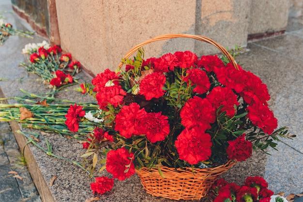 기억의 상징으로 기념물 근처 붉은 카네이션.