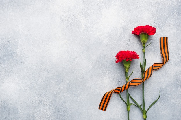 Red carnations and st. george ribbon on a concrete background.