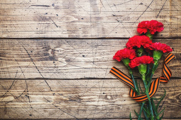 Red carnations and st. george ribbon on wooden background.