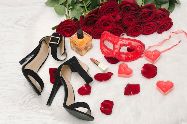 Red carnival mask, a bouquet of red roses, black shoes with heels, candles in the shape of a heart, lipstick, perfume bottle and scattered petals on the white fur.