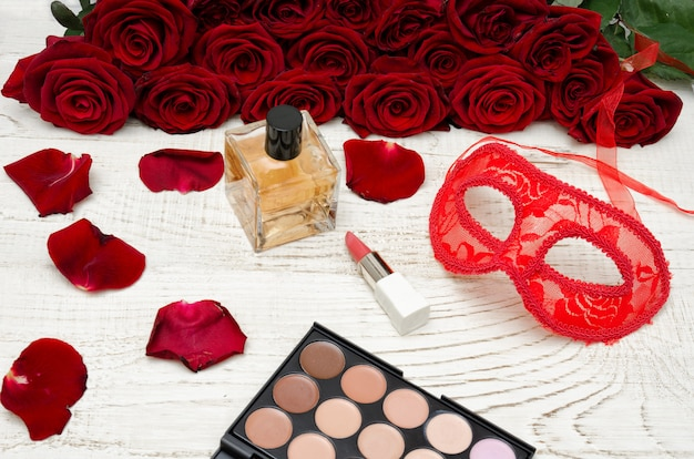 Red carnival mask, perfume and lipstick on a wooden table
