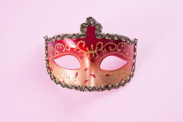 Red carnival mask on pink table