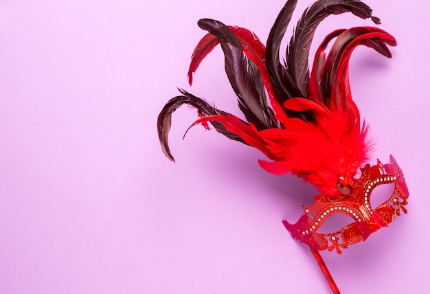Red carnival mask with feathers on pink background with copy space