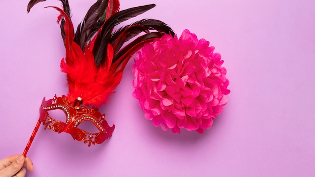 Red carnival mask with feathers on pink background