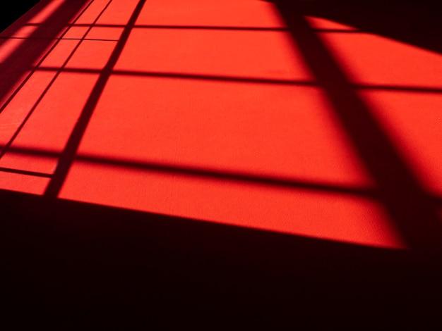 表面に抽象的な線、赤い敷物に日光、床にシルエットと影のあるレッドカーペット