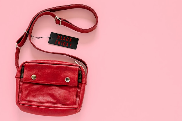 Red carry bag with black price tags on pink background for black friday shopping sale concept.