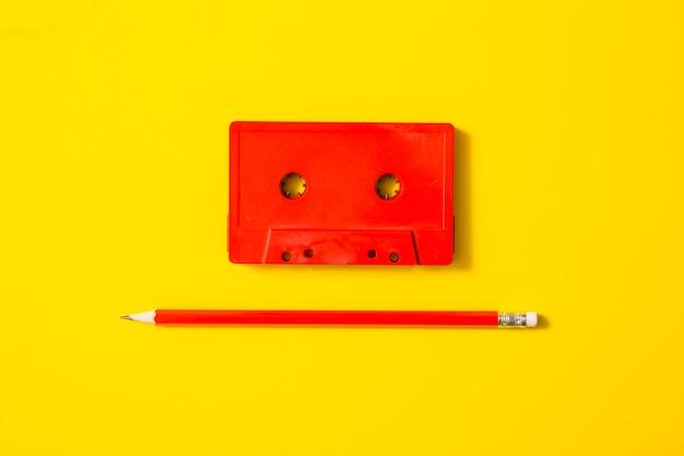 黄色の背景に赤いカセットテープと鉛筆
