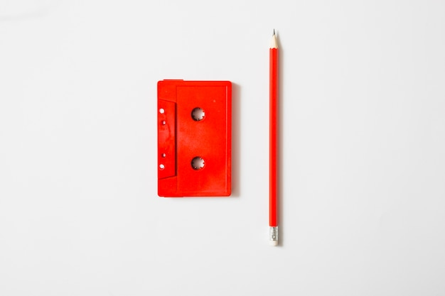 Red cassette tape and pencil on white background