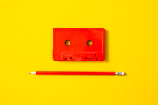 Red cassette tape and pencil on yellow background
