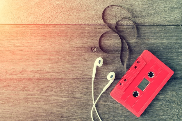 Red cassette tape with earphone over wooden table
