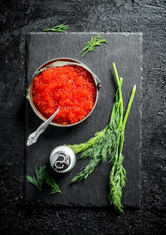 Red caviar in a bowl on a black stone board with salt and dill. on black rustic