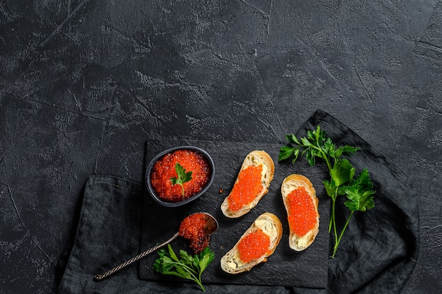Red caviar in bowl and sandwiches on stone board. black surface. top view. copy space