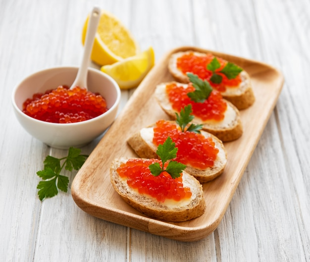 Red caviar in bowl and sandwiches