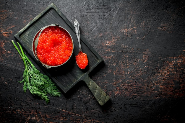 Red caviar in a bowl and a spoon on a cutting board with dill. on dark rustic background