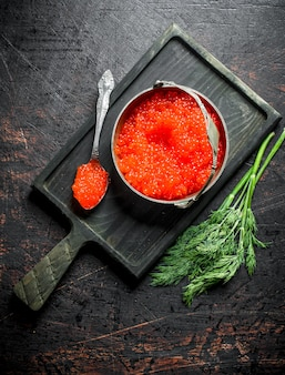 Red caviar in a bowl and a spoon on a cutting board with dill. on dark rustic
