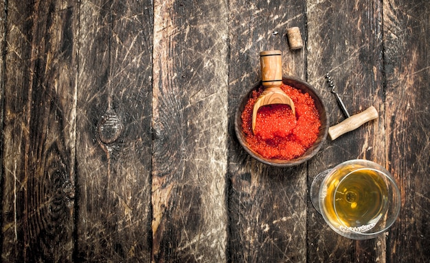 Red caviar in a bowl with a glass of white wine. on wooden background