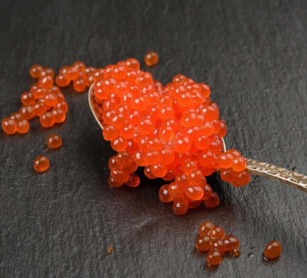Red caviar of chum salmon in a metal spoon on a black background, close up