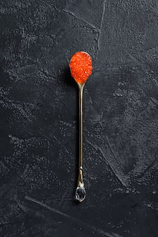 Red caviar in an exquisite spoon. top view.