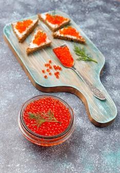 Caviale rosso in una ciotola di vetro e in un cucchiaio, vista dall'alto