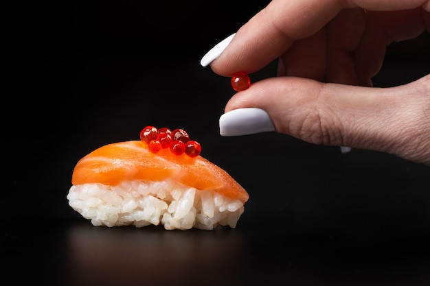 Red caviar in hands over sushi. macro close up.