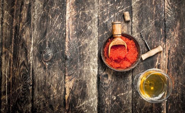 화이트 와인 한 잔 함께 그릇에 빨간 캐 비어. 나무 배경