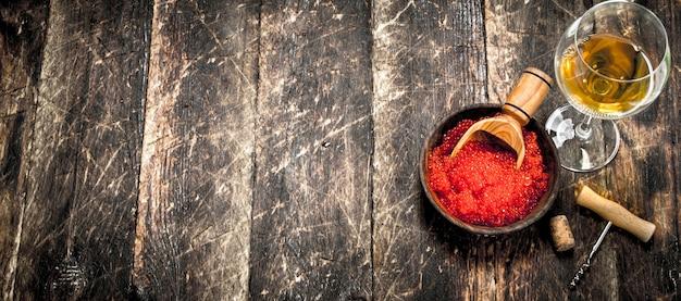화이트 와인 한 잔 함께 그릇에 빨간 캐 비어.