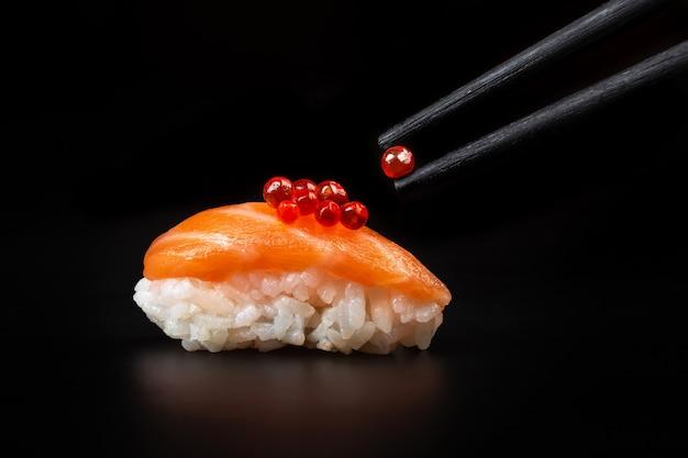 Красная икра в палочках для еды над суши. макро крупным планом.
