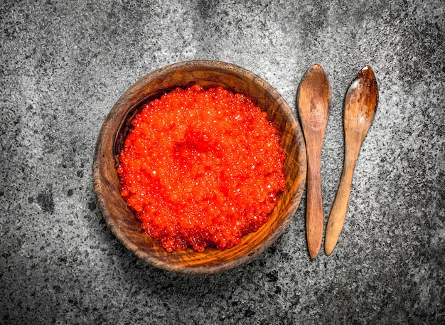 나무 그릇에 빨간 캐 비어입니다. 소박한 배경에
