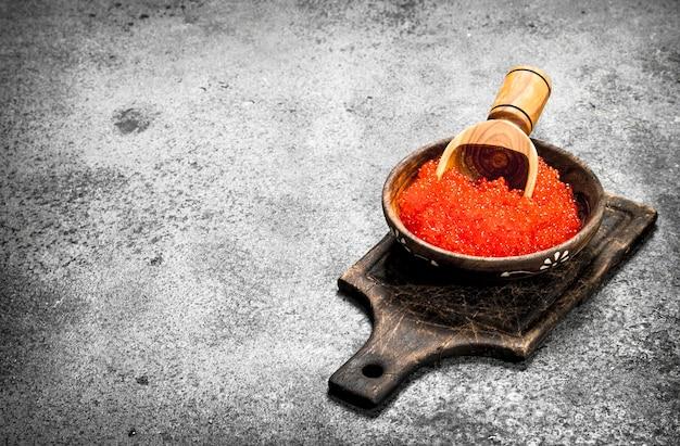 삽으로 나무 그릇에 빨간 캐 비어. 소박한 배경에.