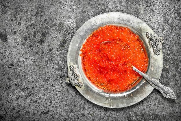 오래 된 접시에 빨간 캐 비어. 소박한 배경에.