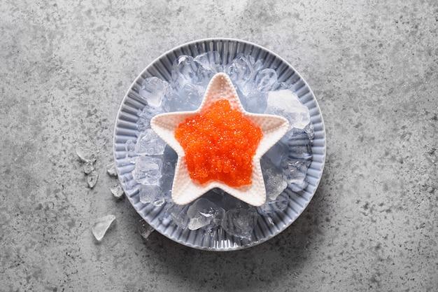 Красная икра в миске в форме звезды подается с кубиками льда для праздничной вечеринки на сером каменном столе. вид сверху.