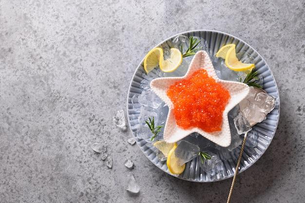 Красная икра в миске в форме звезды подается с лимоном и кубиками льда на сером каменном столе. место для текста. вид сверху.