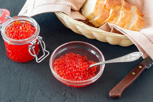 은수저가 든 유리병에 든 레드 캐비어는 빵과 함께 제공됩니다. 해물. 건강한 식생활. 다이어트. 검은 배경.