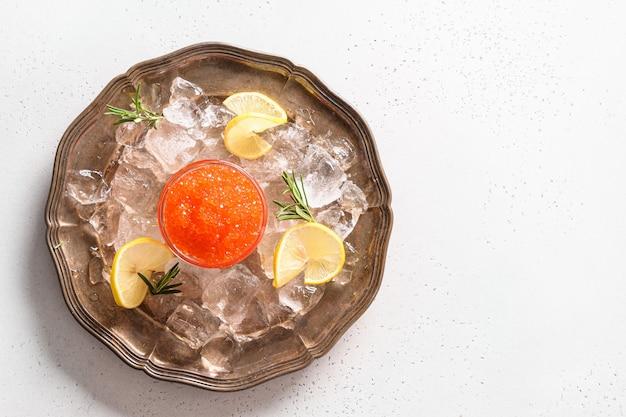 흰색 테이블에 얼음, 레몬, 빈티지 접시에 빨간 캐 비어. 위에서 봅니다. 텍스트를위한 공간.