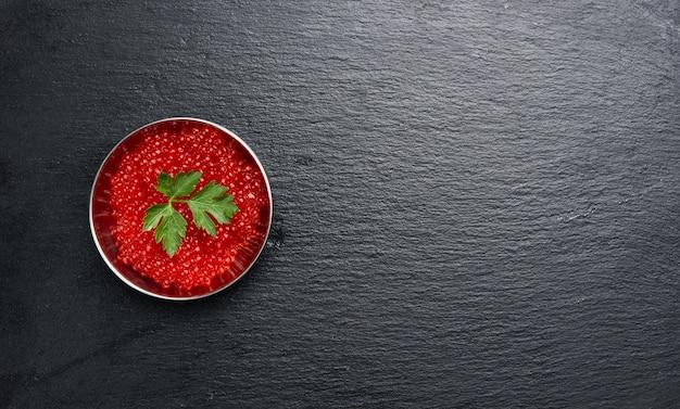 Красная икра кеты в металлической тарелке на черной поверхности, вид сверху, копия пространства