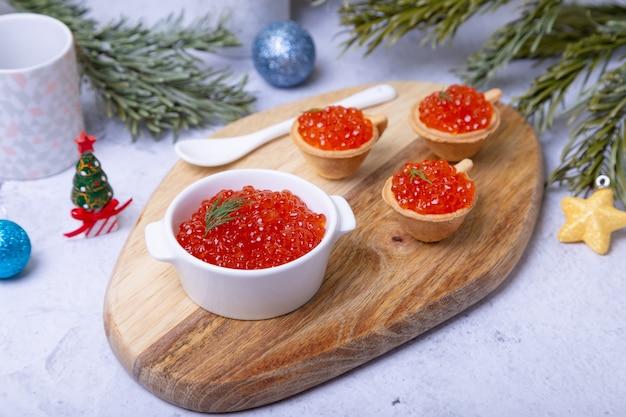 나무 보드에 흰색 그릇에 빨간 캐 비어 (연어 캐 비어)
